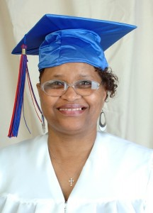 Headshot of Margo Hudson smiling wearing a white top and blue graduation cap