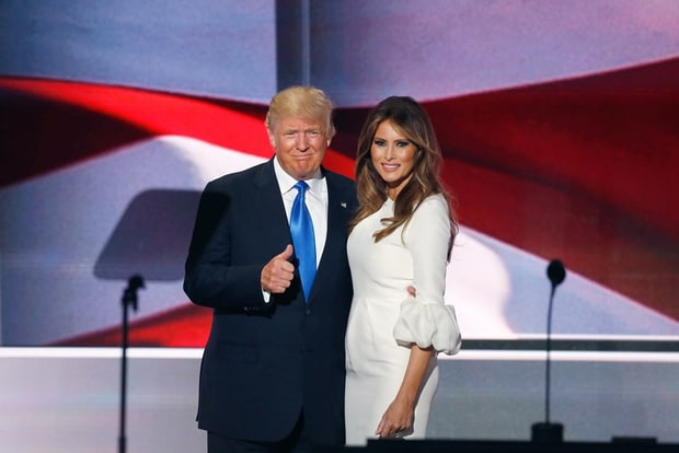 Donald Trump giving a thumbs up while standing with his wife Melania. Donald is in a black suit with white shirt and blue tie. Melania is in a white flowy dress.