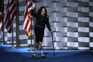 Tammy Duckworth walking on stage with her prosthetic legs, wearing a black suit with American flag in background
