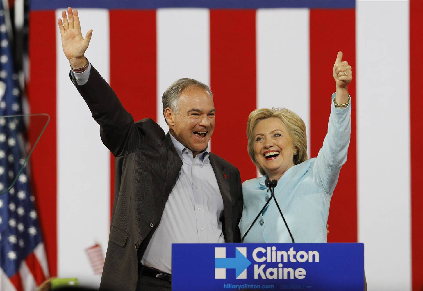 Tim Kaine and Hillary Clinton standing together and smiling; Kaine is waving and Clinton is giving a thumbs up, they are in front of a giant American flag