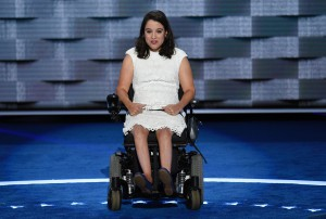 Anastasia Somoza seated in her wheelchair wearing a white lace dress on the DNC stage