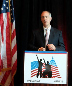 Sen. Bob Casey wearing a black suit talking behind a podium with the text: #ABLE2WORK #ADA26
