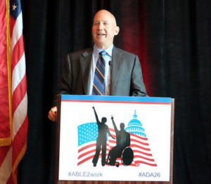 Gov. Jack Markell wearing a gray suit talking behind a podium with the text: #ABLE2WORK #ADA26