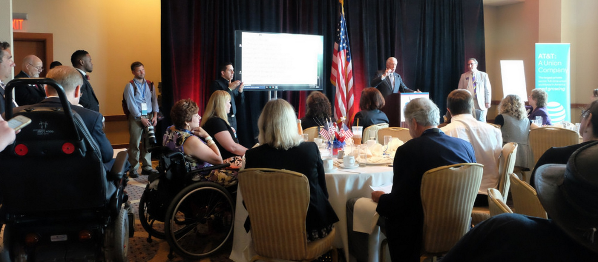 Crowd shot showing people seated in chairs and wheelchairs around tables with speakers standing in front of them, with an ASL interpreter and a screen showing live captioning