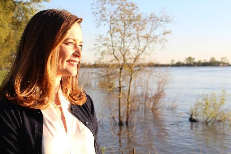 Profile of Caroline Fayard in front of a serene lake with a tree growing in the middle