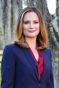 Headshot of Caroline Fayard standing outside wearing blue blazer and pink shirt