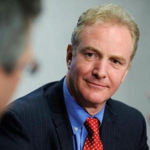 Headshot of Chris Van Hollen in a black suit, blue shirt and red tie