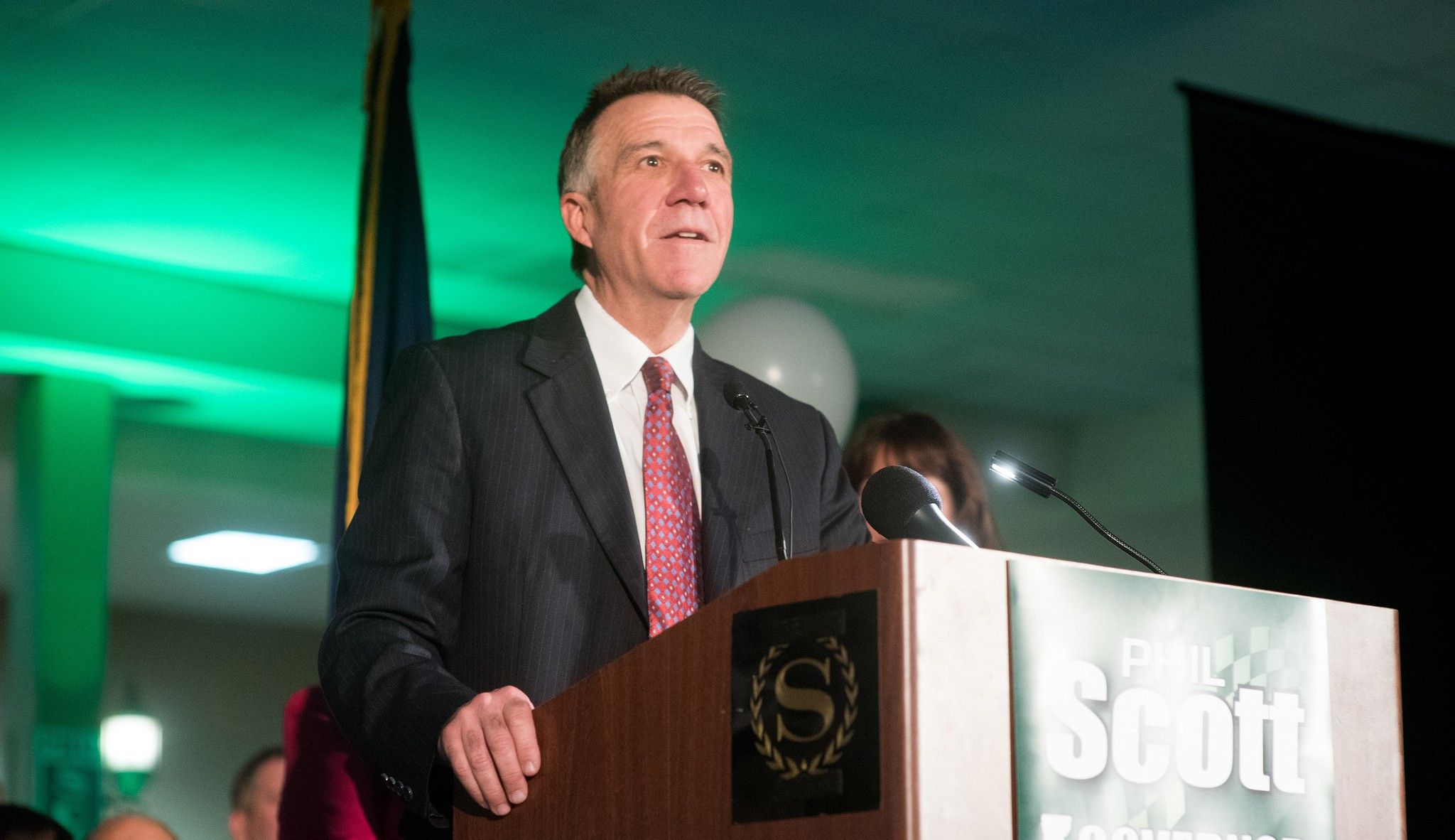 Lt. Gov. Phil Scott speaking behind a podium wearing a suit and a red tie, lighting has green tinge