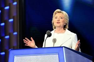 Hillary Clinton standing behind podium, speaking