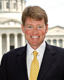 Official portrait of Chris Koster  in a black suit, white shirt and yellow tie