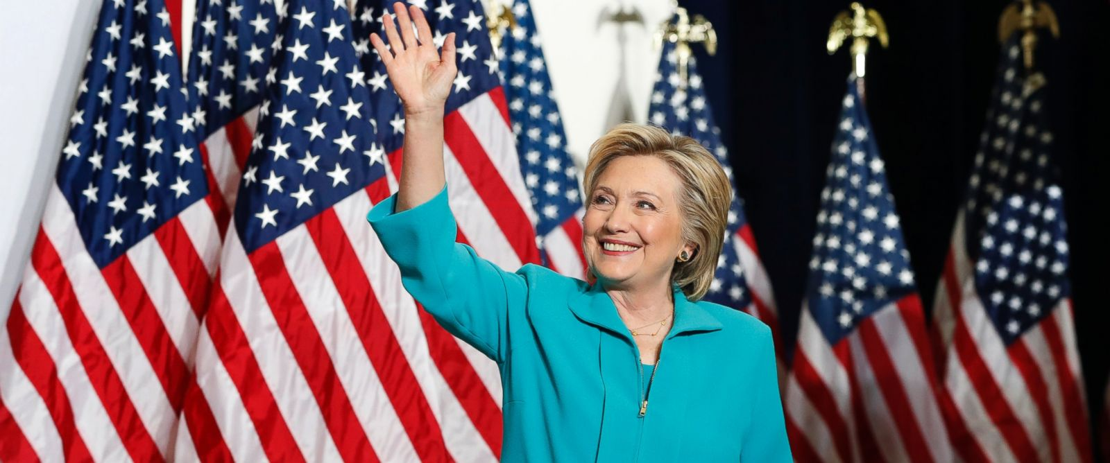 Hillary Clinton waving in front of multiple American flags while standing on stage wearing a teal blue suite