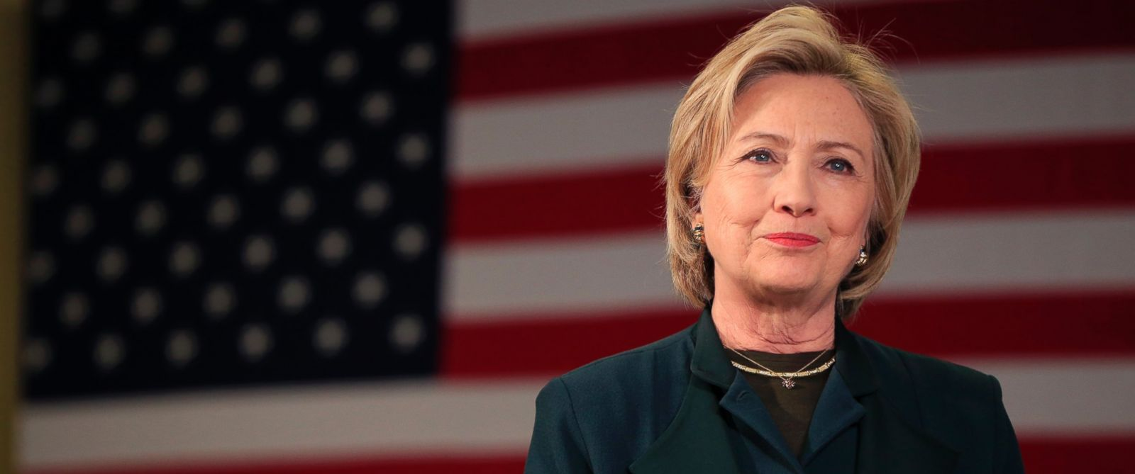 Hillary Clinton smiling with American flag backdrop