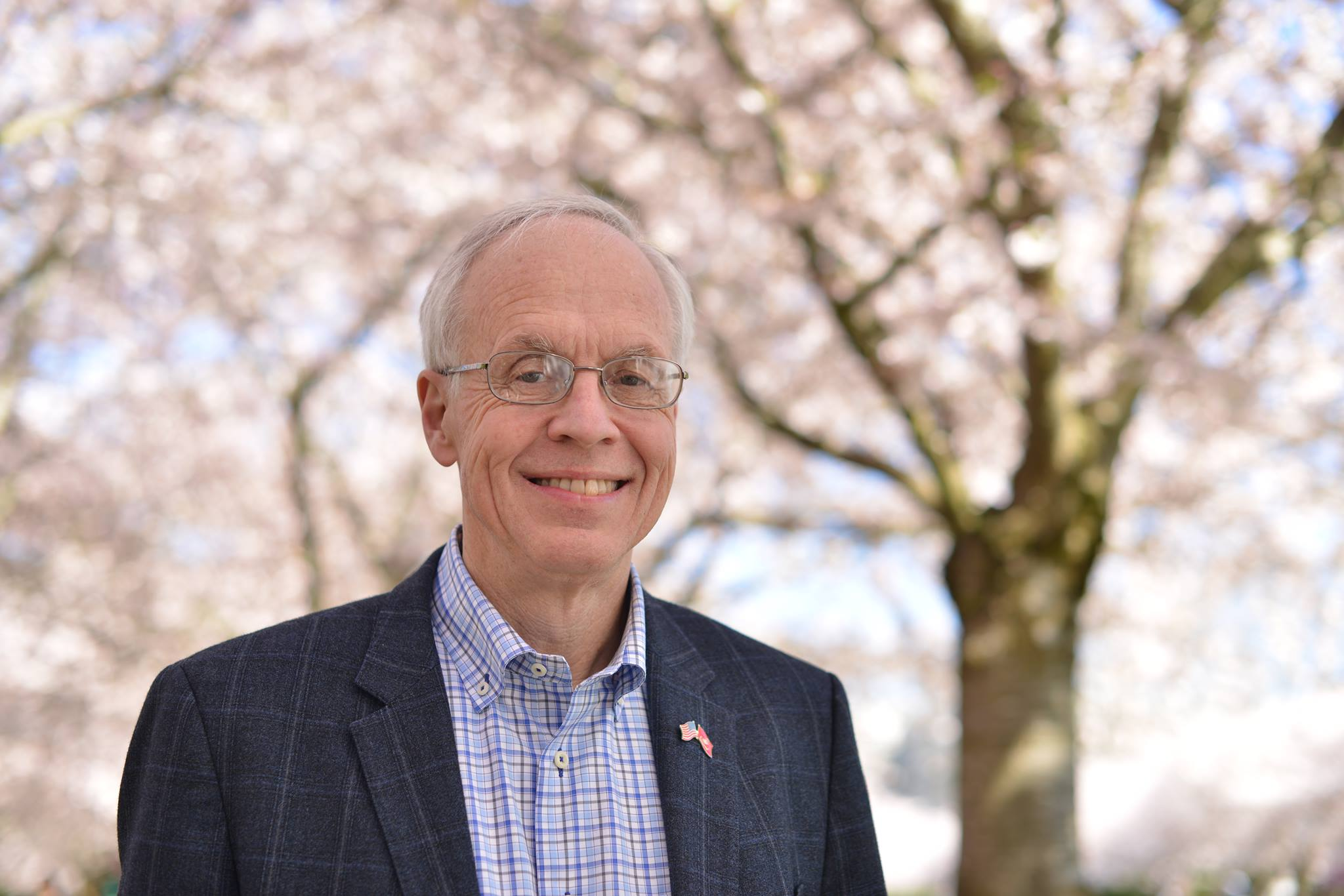 Bud Pierce standing outside in front of cherry blossoms