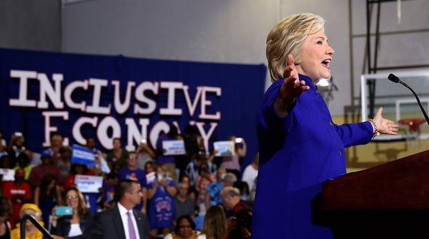 """Hillary Clinton speaking in Orlando with the sign """"inclusive economy"""" behind her"""