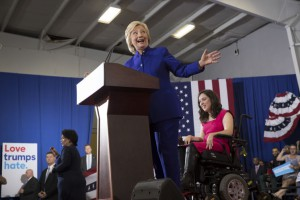 Hillary Clinton speaking in Orlando behind a pocium with Anastasia Somoza seated in a power wheelchair next to her