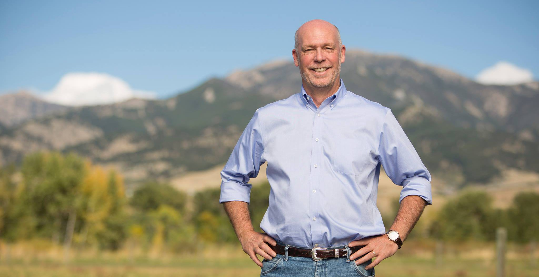 Greg Gianforte standing outside in a blue collared shirt and jeans with mountains in the background