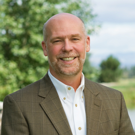 headshot of Greg Gianforte wearing a white collared shirt and brown blazer, outside with a tree in the background