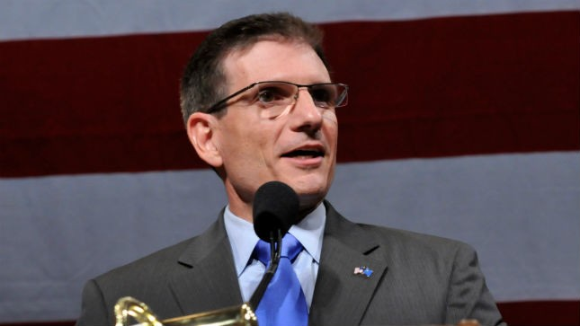 Joe Heck smiling after securing the Republican senate nomination, standing behind a microphone and in front of a large American flag