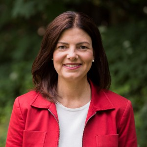 Kelly Ayotte headshot outside wearing white shirt and red jacket