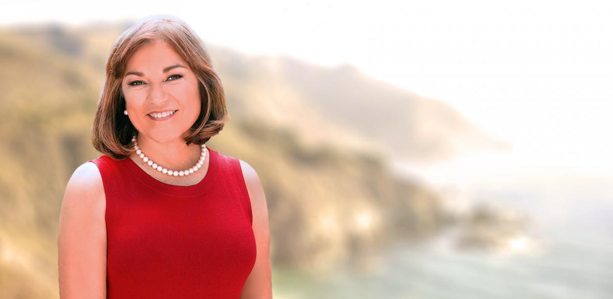 Loretta Sanchez wearing a red dress and pearls standing facing camera with background being ocean