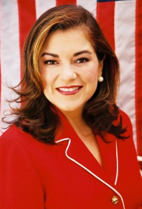 Headshot of Loretta Sanchez in a red suit with American flag as backdrop
