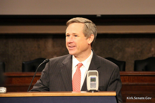Mark Kirk seated behind table with a microphone