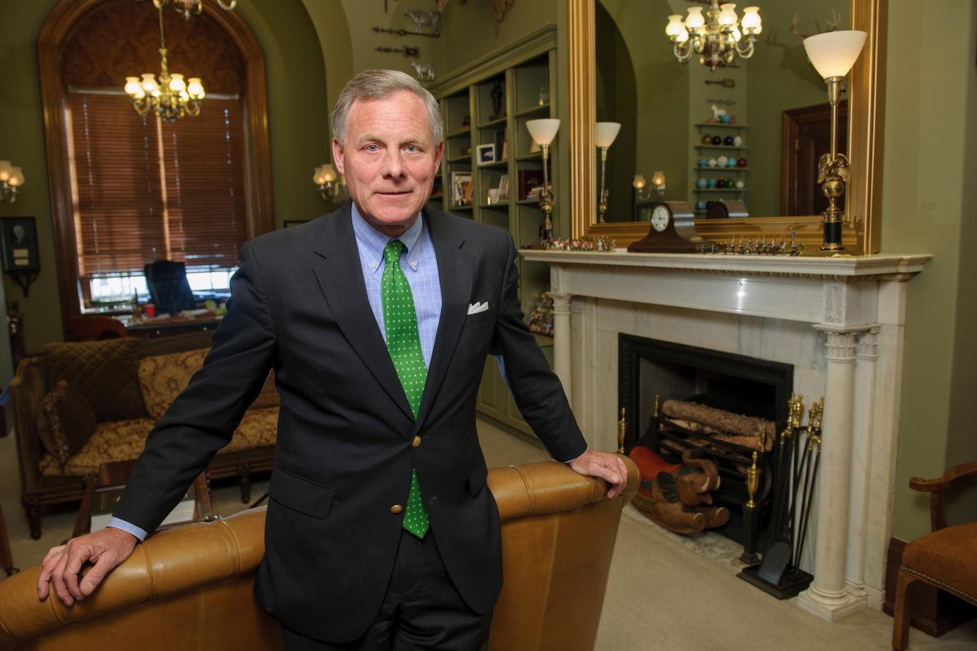 Richard Burr standing in his office wearing a suit with blue shirt and green tie
