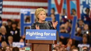 Hillary Clinton speaking behind podium with sign saying Fighting for us