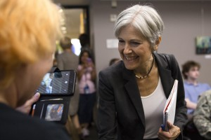 Jill Stein leaning over to shake hands with an attendee