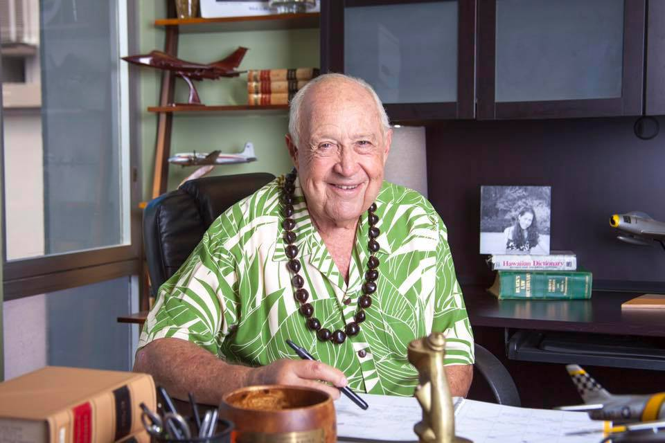 John Carroll wearing a green Hawaiin shirt seated behind a desk