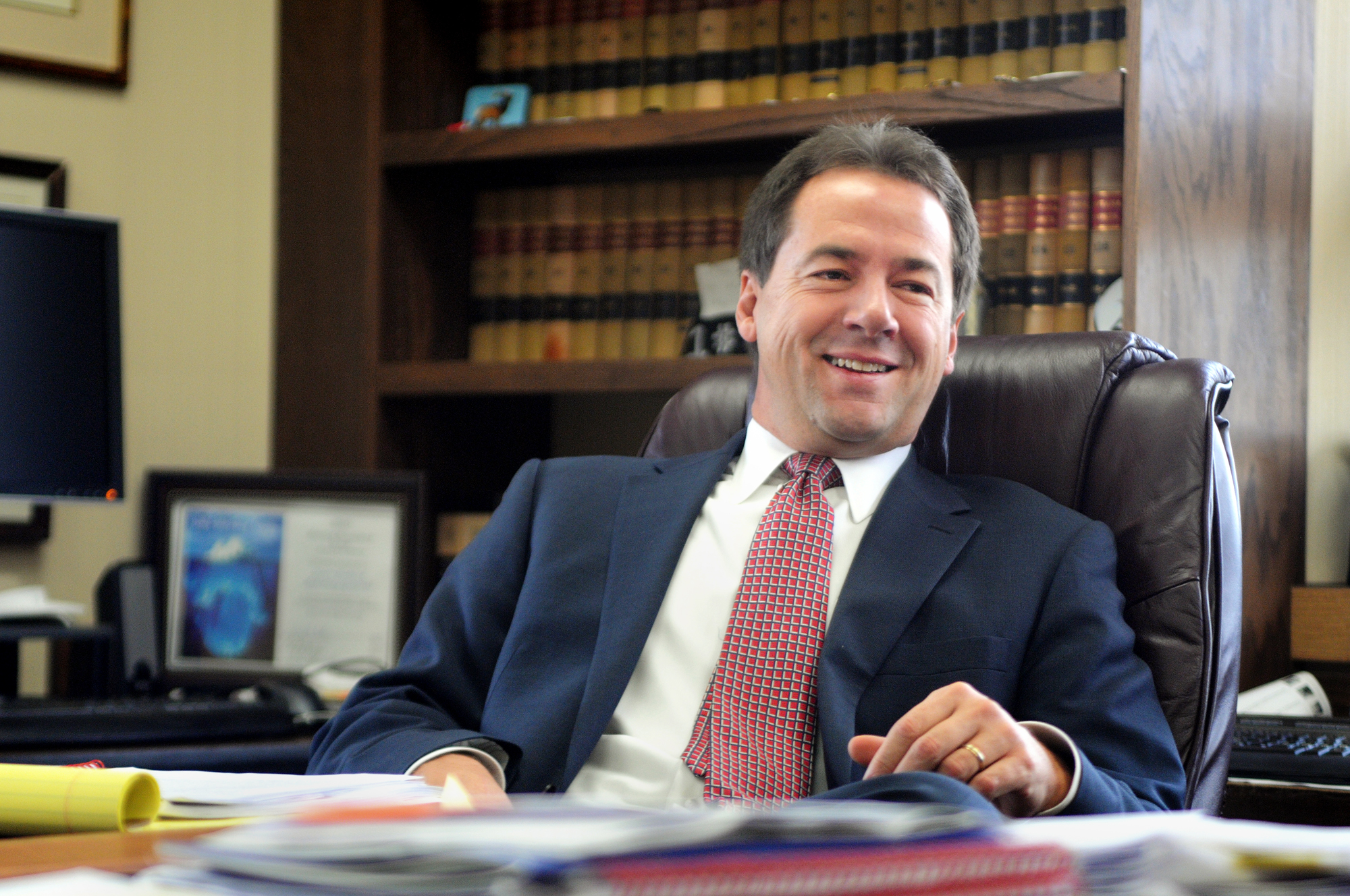 Steve Bullock seated at his desk in his ofice with wall of books in background wearing a black suit with white shirt and red tie
