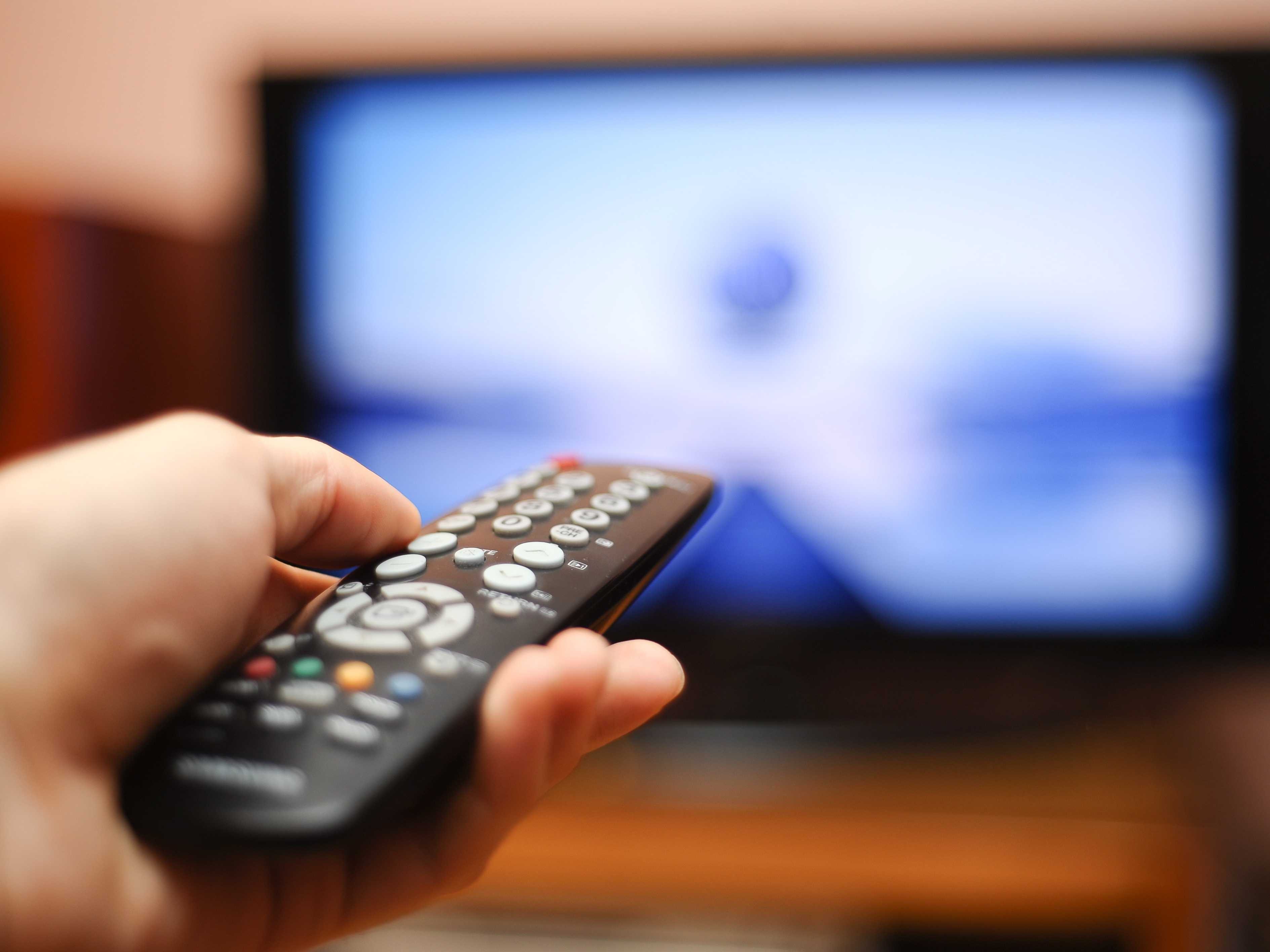 hand holding TV remote in front of blurred out TV screen showing a TV ad