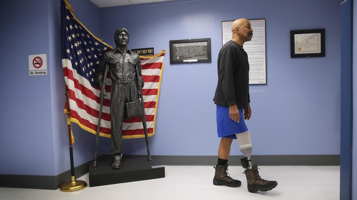 A male veteran who has an amputated leg walks in the hallway. Behind him is a statue without one leg in front of an American flag.