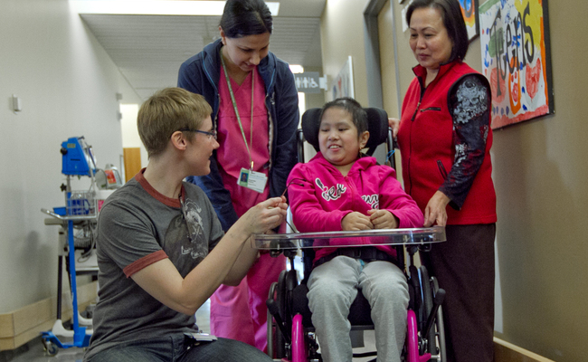A smiling young girl in a wheelchair in a hospital with medical professionals and family members surrounding her