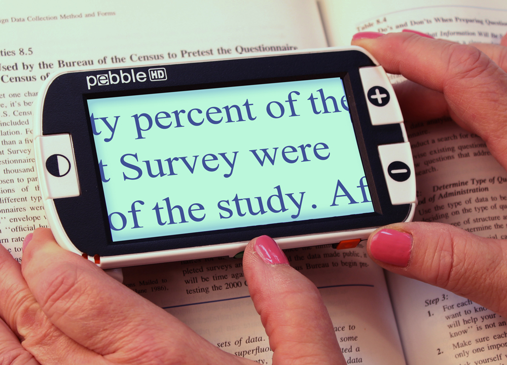 A woman uses a device to magnify words from a book