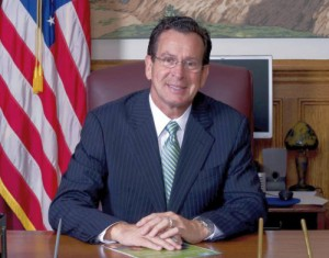 Gov. Dannel Malloy wearing a suit seated behind a large wooden desk with an American flag in the background