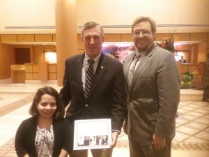 Delaware Governor Carney, RespectAbility's Phillip Pauli, and policy fellow Stephanie Farfan smiling as Governor Carney holds up an award