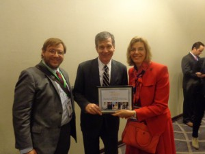 Governor Roy Cooper, Jennifer Mizrahi, and Phillip Pauli smiling, as Gov. Cooper and Jennifer Mizrahi hold an award from RespectAbility