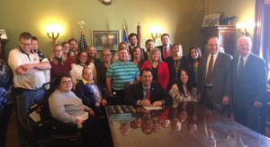 "Governor Scott Walker signs his ""Employment First"" bill surrounded by onlookers"