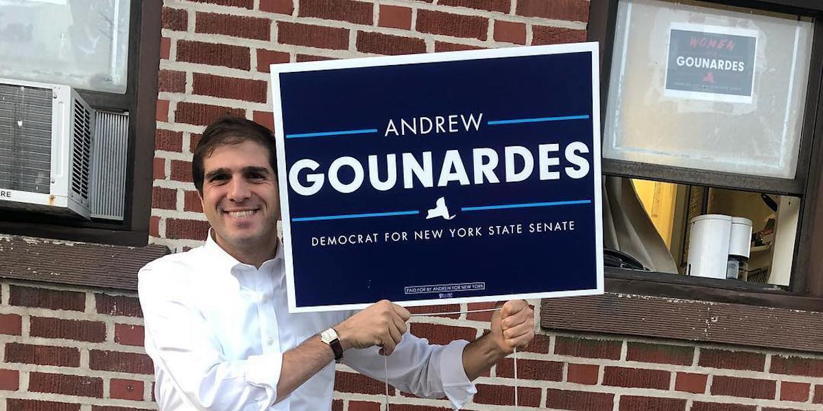 Andrew Gounardes holding up a yard sign for his campaign in front of a brick wall