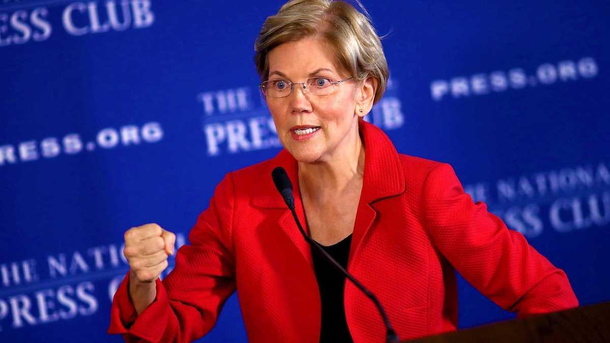 Elizabeth Warren speaking in front of the National Press Club backdrop