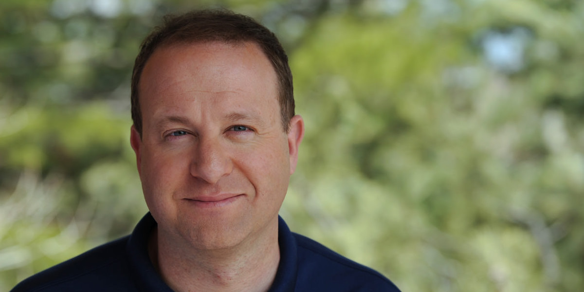 Photo of Jared Polis in front of a blurred green background