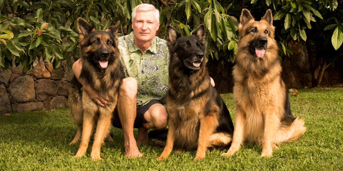 Ron Curtis poses with three dogs in front of some trees