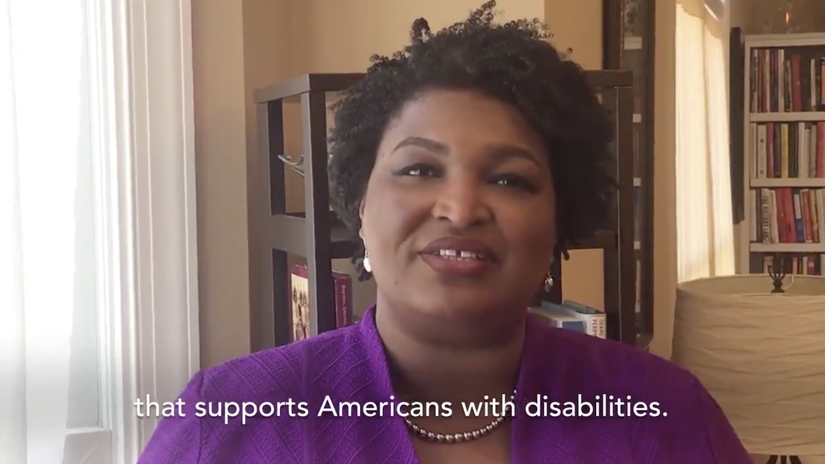 "Still from Stacey Abrams' video addressing the disability community. Subtitle says ""that supports Americans with disabilities."""
