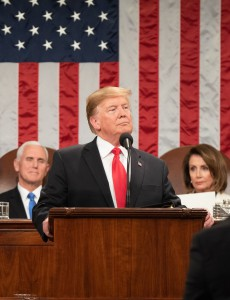 President Trump standing behind the podium of the House of Representatives, with Vice President, Mike Pence (on the left) and the Speaker of the House, Nancy Pelosi (on the right) seated behind him. Behind all three hangs the United States Flag.