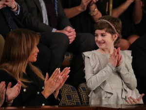 Image Description: Grace Eline, a 10-year-old girl and cancer survivor, is dressed in a ruffled gray, long-sleeved dress, with a pixie haircut and studded headband. She is standing to accept President Trump's recognition of her, while clapping her hands. The First Lady, Melania Trump, who is seated next to her, smiles in her direction, also clapping.