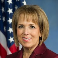 New Mexico Governor Michelle Lujan Grisham smiling in front of an American flag