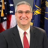 Indiana Governor Eric Holcomb smiling in front of the American flag and the state flag