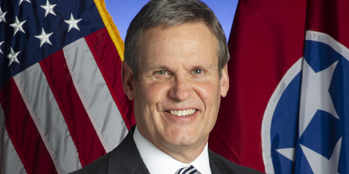 Tennessee Governor Bill Lee smiling in front of an American flag and the Tennessee state flag
