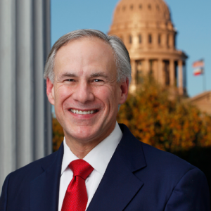 Governor Greg Abbott smiling in front of the Texas state legislature
